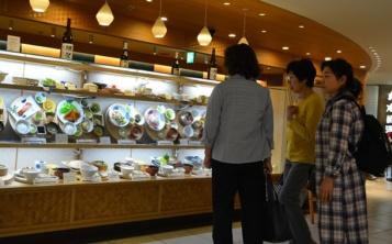 Витрина ресторана, наполненная муляжами блюд, привлекает внимание прохожих