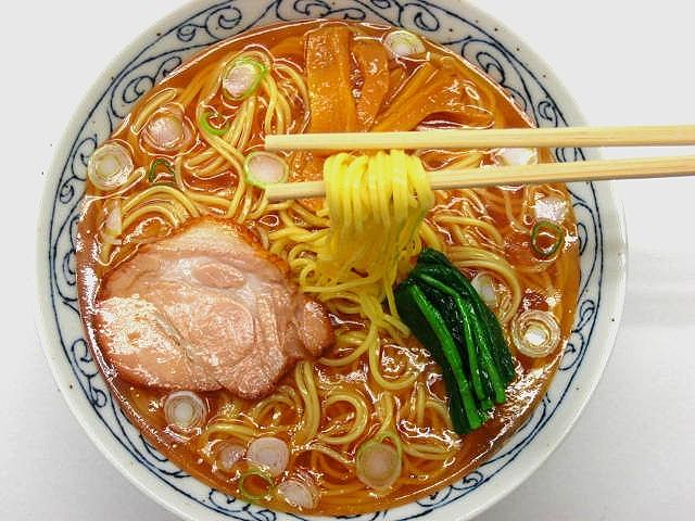 Муляж супа рамен с жареной свининой на палочках (сверху)