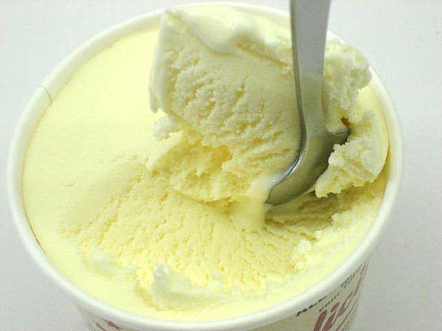 Муляж ванильного мороженого в стаканчике на ложке