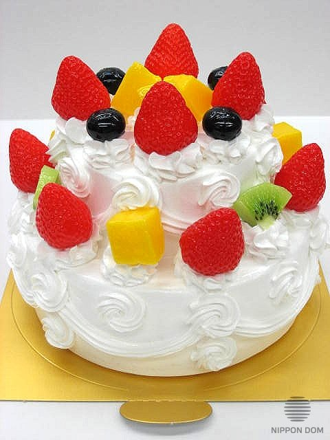 A replica of two-tier cake with mango, bilberry, kiwi and strawberry