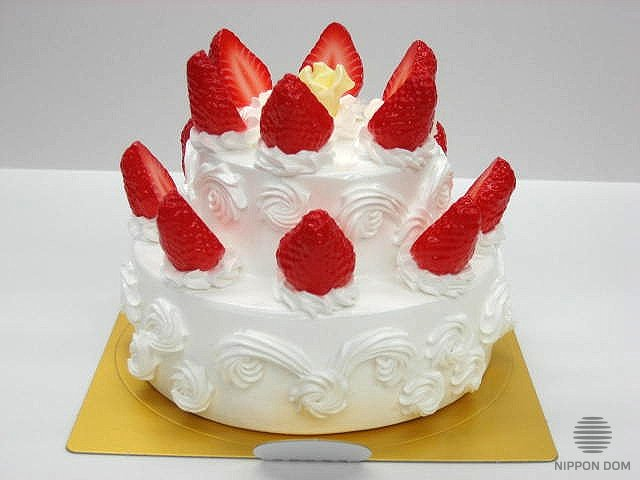 A replica of cake with white chocolate, strawberry