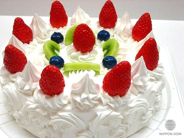 A replica of cake with kiwi, strawberry and bilberry