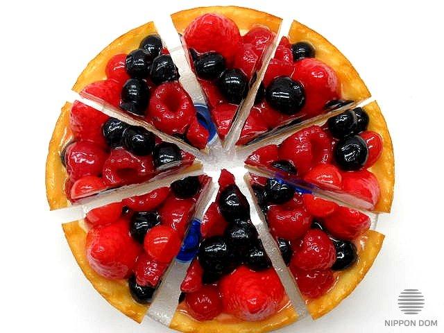 A replica of cheesecake with cranberries, blueberries, raspberries, strawberries