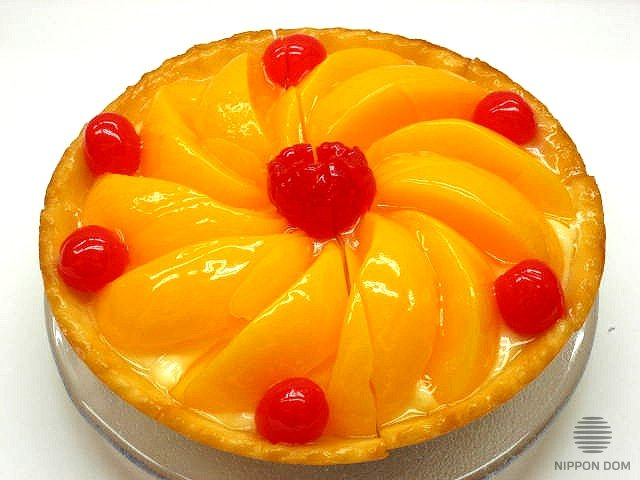 A model of cheesecake with peach and cranberries