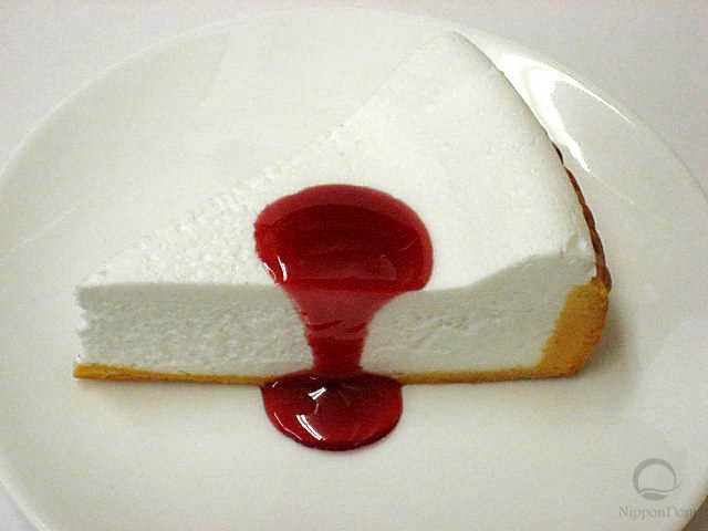 A replica of cheesecake with raspberry sauce